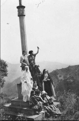 Figura 11. Grup de vuit alumnes, a la creu de l'abat Guimerà de Poblet a Escornalbou, disfressades de personatges literaris. Representats a la fotografia hi ha Beatriu, el Dant, santa Teresa de Jesús, probablement Marguerite Gautier, etc. (1928, AFBD)